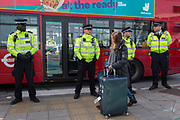 An air passenger finds her way past police officers while environmental activists protesting about Climate Change during the occupation of City Airport (London's Business Travel hub) in east London, the fourth day of a two-week prolonged worldwide protest by members of Extinction Rebellion, on 10th October 2019, in London, England.