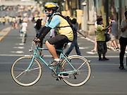 11 DECEMBER 2015 - BANGKOK, THAILAND:  A woman rides her bike on Phloen Chit Road in Bangkok during the warm up for Bike for Dad. More than 527,000 people registered for the Bike for Dad event to honor Bhumibol Adulyadej, the King of Thailand, whose birthday is also celebrated as Father's Day in Thailand. In Bangkok, 99,999 people registered for Bike for Dad. More than 418,000 people registered for Bike for Dad rides in the provinces outside Bangkok and 9,805 participated in Bike for Dad events outside of Thailand. His Royal Highness Crown Prince Maha Vajiralongkorn, the heir apparent to the Thai crown, led the bike ride in Bangkok. The Bangkok route was 29 kilometers long (18 miles) and traveled through Bangkok and across the Chao Phraya River into Thonburi. Bike for Dad events were held across Thailand.    PHOTO BY JACK KURTZ