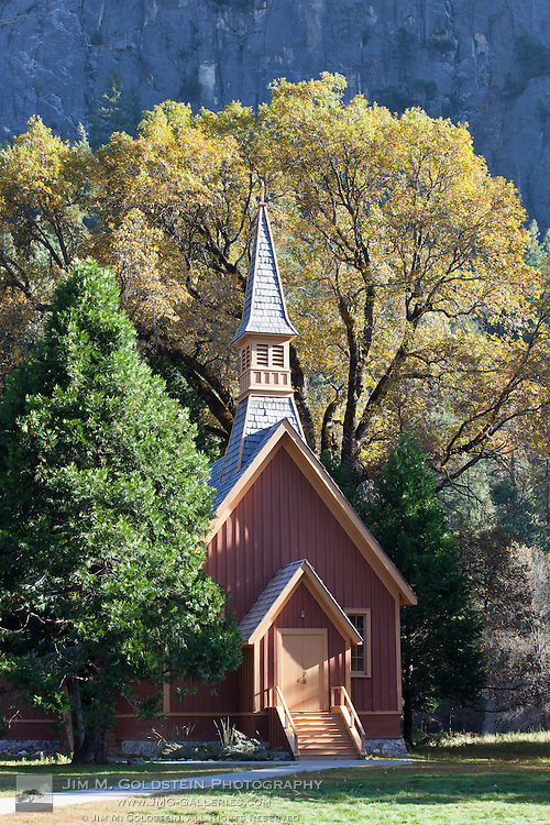 Fall view of Yosemite Chapel under yellow trees in Yosemite National Park, California
