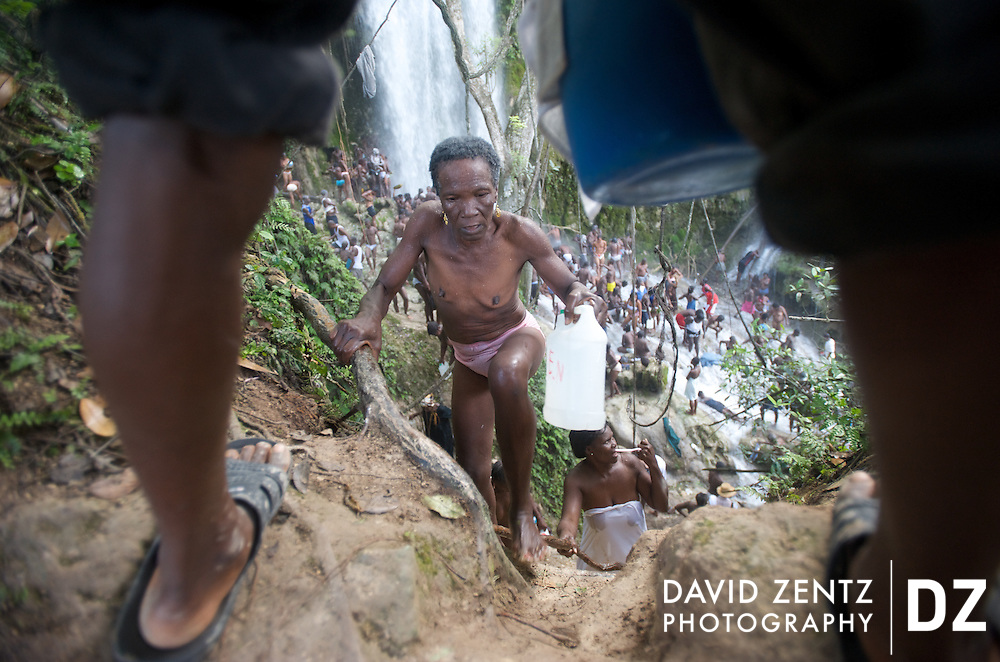 Pilgrims climb up a steep dirt wall to a cliff overlooking the waterfall at Saut D'eau in central Haiti during an annual voodoo pilgrimmage held there each July. Many carry out jugs of water....