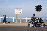 Dun Laoghaire Seafront in Dublin Ireland. Couple walking along seafront and motorbike waiting at traffic lights. Sign for the car ferry to Hollyhead in Wales.