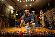 Albert Borokhim unrolls a Persian Bijar rug and poses for a portrait inside Borokhim's Oriental Rugs on Monroe Street, Monday, April 24, 2017. Borokhim moved to the United States nearly fifty years ago and opened his Persian rug store in 1972.