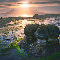 The sun sets over the Isle of Rum looking northwest from the Bay of Laig, Isle of Eigg