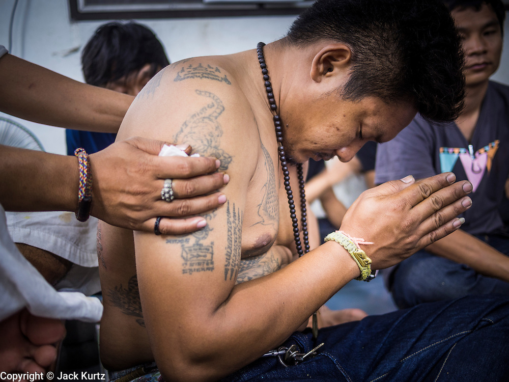 "15 MARCH 2014 - NAKHON CHAI SI, NAKHON PATHOM, THAILAND: An archan holds a man who is praying after the archan finished giving the man a sak yant tattoo at Wat Bang Phra. Wat Bang Phra is the best known ""Sak Yant"" tattoo temple in Thailand. It's located in Nakhon Pathom province, about 40 miles from Bangkok. The tattoos are given with hollow stainless steel needles and are thought to possess magical powers of protection. The tattoos, which are given by Buddhist monks, are popular with soldiers, policeman and gangsters, people who generally live in harm's way. The tattoo must be activated to remain powerful and the annual Wai Khru Ceremony (tattoo festival) at the temple draws thousands of devotees who come to the temple to activate or renew the tattoos. People go into trance like states and then assume the personality of their tattoo, so people with tiger tattoos assume the personality of a tiger, people with monkey tattoos take on the personality of a monkey and so on. In recent years the tattoo festival has become popular with tourists who make the trip to Nakorn Pathom province to see a side of ""exotic"" Thailand.   PHOTO BY JACK KURTZ"