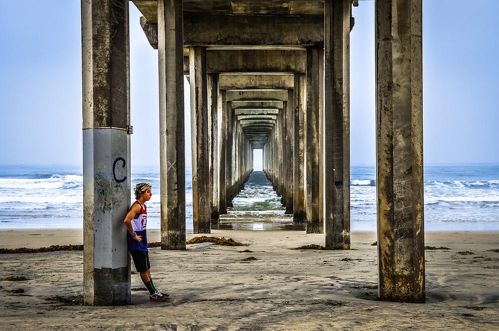 A person taking a break from a beach run.