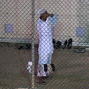 """A detainee performs the Muslim call to prayer for the rest of detainees in Camp 4 at the detention facility in Guantanamo Bay, Cuba. Camp 4 is a communal style camp where more compliant detainees live in small groups and have access to a more open air environment. Approximately 250 """"unlawful enemy combatants"""" captured since the September 11, attacks on the United States continue to be held at the detention facility.(Image reviewed by military official prior to transmission)"""