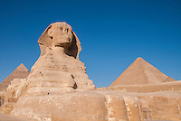 View of the Sphinx from it's feet with 2 pyramids in the background, in Giza, Egypt.