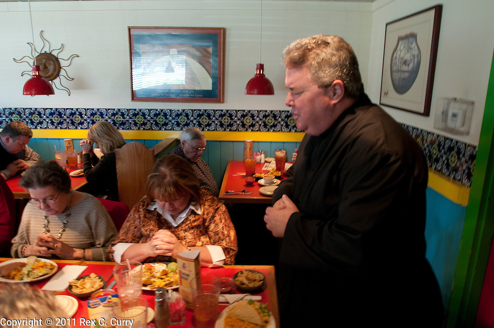 Father Charles Hough, right, , says grace during lunch after leading his congregation in morning prayer at the St. John Vianney Parish in Cleburne, Tx. Sunday Jan. 1, 2012.  Hough is an Episcopal priest in the process of becoming ordained as a Catholic priest.  The parish is temporarily operating out of a private business..