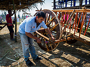 17 FEBRUARY 2018 - BAN LOT, PHETCHABURI, THAILAND: A man repairs an ox cart before a race in Ban Lat, a community about three hours south of Bangkok. The ox cart races are almost 100 years old, and date back to the reign of King Rama V. The races are run on a 100 meter long straightaway course.   PHOTO BY JACK KURTZ