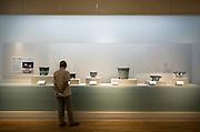 A visitor looks at Seto plant pots on display at the Saitama Omiya Bonsai Museum of Art in Saitama, Japan on 15 Aug. 2011..Photographer: Robert Gilhooly