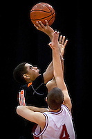 JEROME A. POLLOS/Press..Post Falls High's Shawn Reid puts up a shot in front of Madison High's Rhett Robison during Friday's game at the state 5A boys basketball tournament at the Idaho Center in Nampa.