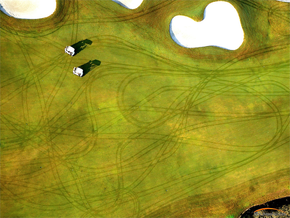 Aerial view of two golf carts and tracks on dew covered golf course.  Weston Hills Country Club, WEston, Fl