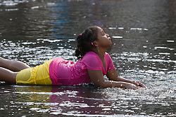 Cute little African American girl in colorful clothes lying in puddle of water on a warm summer day
