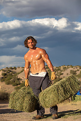 hot shirtless muscular man with hay bale outdoors at sunset