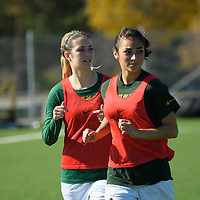 2nd year forward Alex Ensign (22) and 2nd year midfielder Brigit Sinaga (24) of the Regina Cougars warmup on the sideline during the women's soccer home game on October 1 at U of R Field. Credit: Arthur Ward/Arthur Images