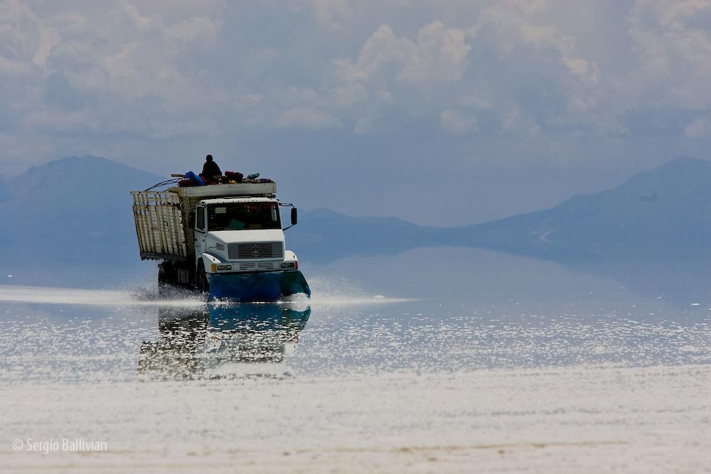 A truck drives across the flooded Salar de Uyuni salt flats in Bolivia