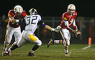 Marion's Trevor Hardman (7) tries to avoid Central DeWitt's Jacob Thumann (32) as he rolls out during their second round playoff football game at Thomas Park Field in Marion on Monday, October 29, 2012.