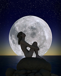 Young woman sitting on a rock against an enormous full moon rising above the horizon on an expansive ocean