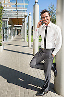 Smiling businessman using mobile phone while leaning on column outside office