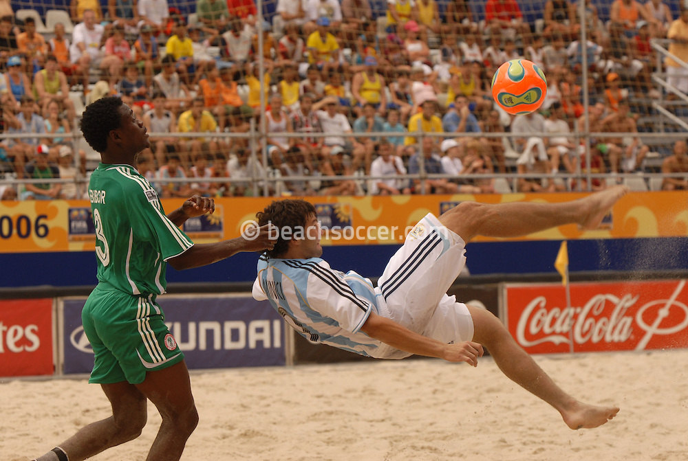 Football-FIFA Beach Soccer World Cup 2006 - Group D-ARG_NGA - Opening match of the Beachsoccer World Cup 2006. Facundo Minici, observed by Peter Ebibor, strikes to goal and hit the score- Rio de Janeiro - Brazil 02/11/2006<br />Mandatory credit: FIFA/ Marco Antonio Rezende.