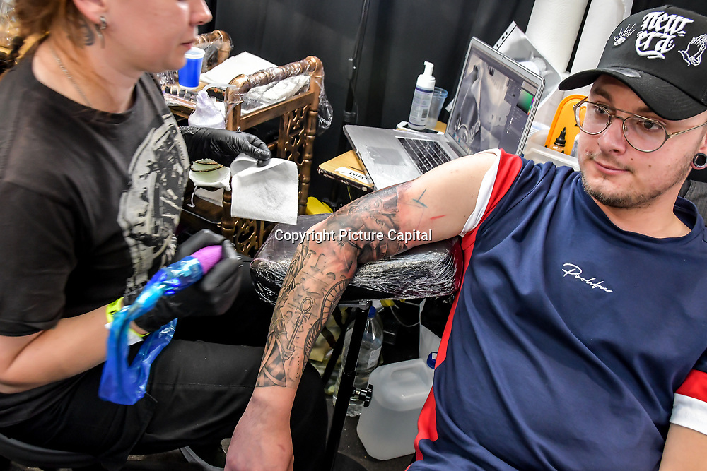 Artist Ivona Iva tattoo a client at The Great British Tattoo Show, London, UK