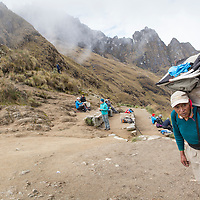Peru, Porter carries heavy load at 13,800' summit of Dead Woman's Pass along Inca Trail to Machu Picchu along Urubamba River