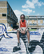 Young boy sitting on a brick wall with graffiti.