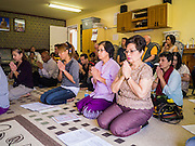 "11 MARCH 2012 - CHANDLER, AZ:     People participate in Buddhist chanting in the ""bot"" or ordination hall during Makha Bucha Day services at Wat Pa in Chandler, AZ, Sunday. Magha Puja (also spelled Makha Bucha) Day marks the day 2,500 years ago that 1,250 Sangha came spontaneously to see the Buddha who preached to them on the full moon. All of them were ""Arhantas"" or Enlightened Ones who had been personally ordained by the Buddha. The Buddha gave them the principles of Buddhism, called ""The Ovadhapatimokha."" Those principles are: to cease from all evil, to do what is good, and to cleanse one's mind. It is one of the most important holy days in the Theravada Buddhist tradition. At the temple, people participate in the ""Tum Boon"" (making merit by listening to the monk's preaching and giving a donation to the temple), the ""Rub Sil"" (keeping of the Five Precepts including the abstinence from alcohol and other immoral acts) and the ""Tuk Bard"" (offering food to the monks in their alms bowls). It is a day for veneration of the Buddha and his teachings. It's a legal holiday in Thailand, Laos, Cambodia and Myanmar (Burma).     PHOTO BY JACK KURTZ"