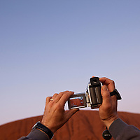 Australia, Northern Territory, Uluru - Kata Tjuta National Park, Tourist shooting video of Ayers Rock  before sunrise