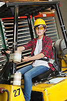 Asian female industrial worker driving forklift truck