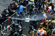Riot Police in Portland spray the crowd with pepper spray and then attempt to forcibly move them back to the corner of SW 5th and Taylor. A man in a motorized chair (bottom left) was to attend the President Bush event and was confused by the crowd as protesting. Riot police circled him and then continued with the further deployment of  pepper balls, rubber bullets and bean bag rounds.