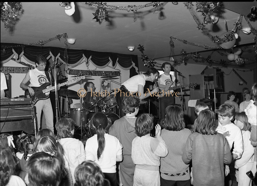 Christmas Party With Johnny Logan..1986..16.12.1986..12.16.1986..16th December 1986..At the 'Embankment',Tallaght, a charity Christmas Party was held for deprived children of the area. The main attraction was the singer and entertainer Johnny Logan,who with his band,entertained the children. Santa Claus took time off from his busy schedule to give a present to all the boys and girls. A great time was had by all...Image shows Johnny serenading a yopung lady at the front of the stage.