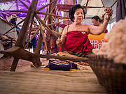 19 APRIl 2014 - BANGKOK, THAILAND: A woman demonstrates how to use a traditional spinning wheel at the Rattanakosin Festival in Bangkok. Rattanakosin is the name of the man made island that is the heart of the old city. Bangkok was formally founded as the capital of Siam (now Thailand) on 21 April 1782 by King Rama I, founder of the Chakri Dynasty. Bhumibol Adulyadej, the current King of Thailand, is Rama IX, the ninth King of the Chakri Dynasty. The Thai Ministry of Culture organized the Rattanakosin Festival on Sanam Luang, the royal parade ground in the heart of the old part of Bangkok, to celebrate the city's 232nd anniversary.    PHOTO BY JACK KURTZ
