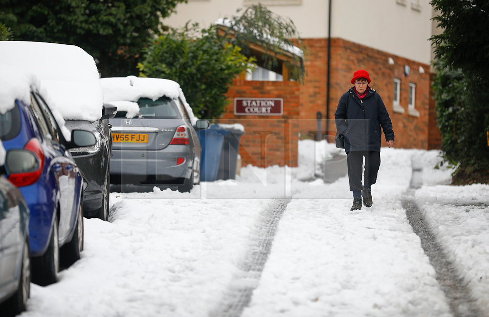 © Licensed to London News Pictures. 11/12/2017. Amersham, UK. A woman in winter clothing walks through snow  in the town of Amersham Station in Buckinghamshire. Further snowfall has hit parts of the south east of England causing travel disruption. Photo credit: Tom Nicholson/LNP