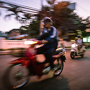 Panning shot of motorbike speeding along a local street in Chiang Mai