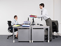 Businessman passing off work to female colleague in office