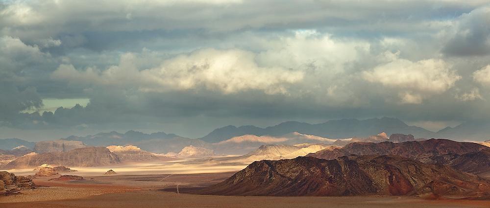 Dark clouds over eroded shale hills in Wadi Rum, Jordan.
