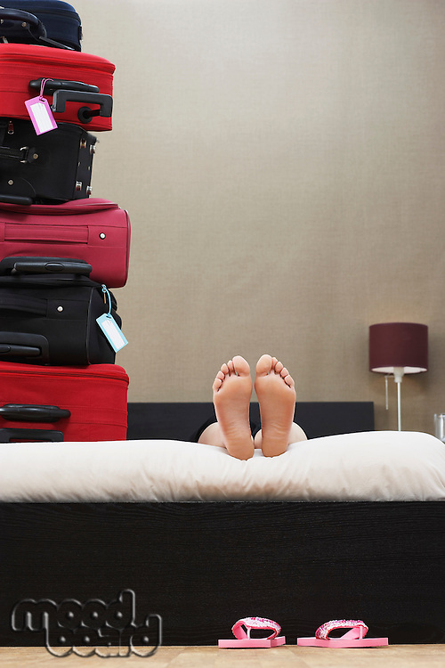 Person lying down in bed next to stack of suitcases