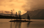 Canada, Alberta,Banff.  Stormy sky over moutnain lake with small island.