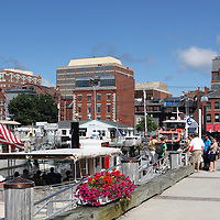 View of Long Wharf Pier and Portland , Maine, USA waterfront. Long Wharf Pier is the departure point for several scenic cruises of Casco Bay. Tourists are seen boarding a boat for one such cruise.