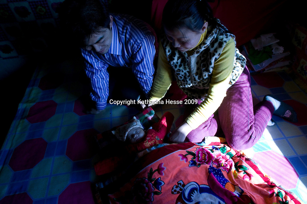 NORTHERN HEBEI PROVINCE, JANUARY 26, 2009:<br /> Mr Lu, a textile worker in Beijing, and his wife admire their newborn baby while on home leave.<br /> Lu went to Beijing 8 years ago as he couldn't find a job in China's countryside.<br /> He was employed in a textile factory that went banctrupt last October. Lu and his 63 colleagues were still owed payment for 4 months, but their boss refused to pay them. They didn't know the law, nor did any of them have a contract.  <br /> At the end of January, Lu and his co-workers went to see the bosses' mother to negociate, then the union and in the end the government. They were threatened with jail . At the end of the day , a man from the union came by ( on behalf of the government )and all but an underaged worker received their due salaries.<br /> Now Lu is unemployed like 20 milion other migrant workers in China who have been laid off as a result of the financial crisis.<br /> <br /> <br /> China's Communist Party  which will celebrate its 60th anniversary in October, currently faces its biggest challenge since the beginning of the economic reforms 30 years ago  : &quot; The phase of  rapid economic growth is over. For the first time the government is threatened with a  mistrust of a wide section of the population&quot;, warns the Communist party's Shang Dewen in Beijing.   <br /> Not only the China's poorest worry about the furture, but as well China's middle class is concerned about the crisis.     1,5 Millionen university graduates didn't find a job until the end of 2008  and this summer there'll be an additional  6,1 Million new graduates. More than 12 percent of university graduates face unemployment in 2009.