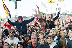 © Licensed to London News Pictures. 26/06/2015. Pilton, UK.  Festival goers cheer as the Libertines appear on the Pyramid stage at Glastonbury Festival 2015 as a surprise act, filling the slot vacated by Florence and the Machine who moved to the headline slot after Foo Fighters pulled out, on Friday Day 3 of the festival.  This years headline acts include Kanye West, The Who and Florence and the Machine, the latter being upgraded in the bill to replace original headline act Foo Fighters.   Photo credit: Richard Isaac/LNP