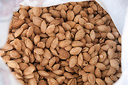 A pile of freshly roasted unshelled almonds