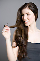 Woman twisting long brown hair