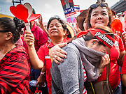 20 NOVEMBER 2013 - BANGKOK, THAILAND:  A Red Shirt comforts one of her friends who wept when the Thai Constitutional Court would not force the dissolution of the government of Prime Minister Yingluck Shinawatra. Thousands of Red Shirts, supporters of the Pheu Thai ruling party in Thailand, gathered in Rajamangala Stadium in suburban Bangkok to listen to the Thai Constitutional Court deliver its verdict against the government. The court ruled that the recent efforts by the government to pass a blanket amnesty bill violated the Thai Constitution but the court did not order the party to disband or the dissolution of the government, which had been widely feared.    PHOTO BY JACK KURTZ