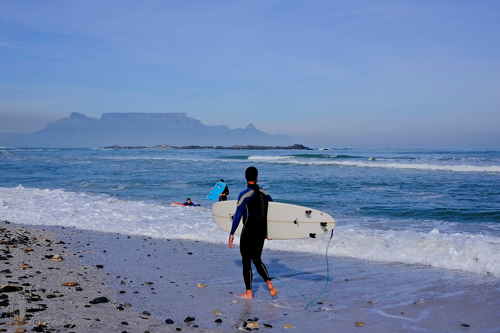 Table Mountain,Cape Town, South Africa. Surfers enjoy an early morning wave. Mussel and other shells litter the beach after heavy seas. A blanket of smog covers the base of Table Mountain in the early winter morning.