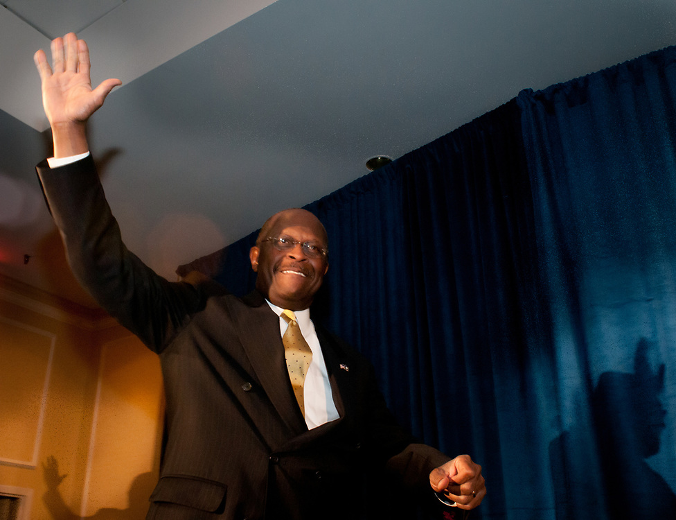 Presidential hopeful Herman Cain waves to the crowd as he takes the stage during a campaign Rally in the Radisson Hotel in Nashua, NH.