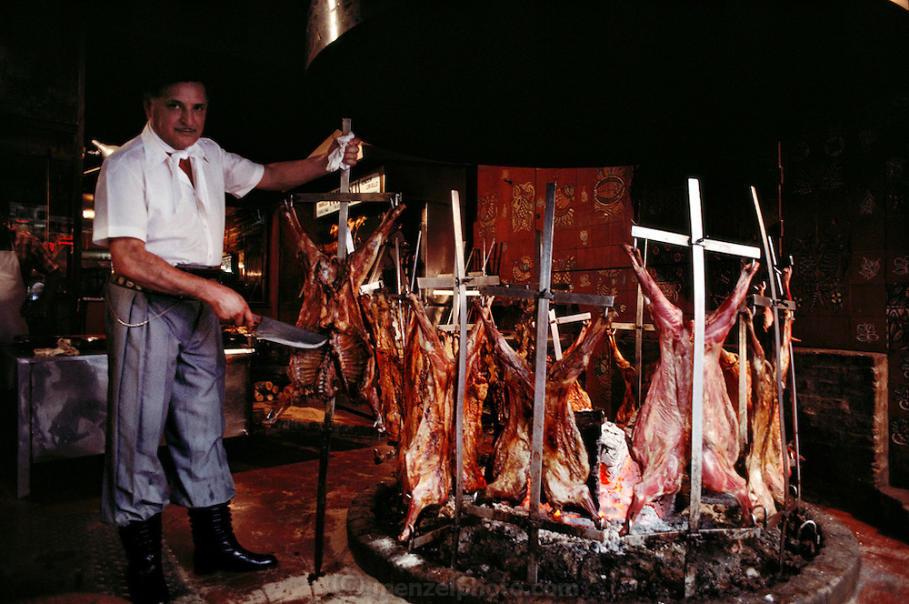 Meat being grilled in an open pit in a window display to attract hungry pedestrians at La Estancia restaurant. Buenos Aires, Argentina.