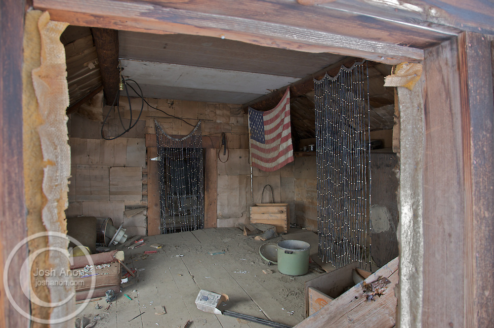 An American flag hands with beads in an empty cabin in the ghost town of Old Bettles, Alaska.