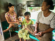 26 OCTOBER 2015 - YANGON, MYANMAR: A family rides the Yangon Circular Train. The Yangon Circular Railway is the local commuter rail network that serves the Yangon metropolitan area. Operated by Myanmar Railways, the 45.9-kilometre (28.5 mi) 39-station loop system connects satellite towns and suburban areas to the city. The railway has about 200 coaches, runs 20 times daily and sells 100,000 to 150,000 tickets daily. The loop, which takes about three hours to complete, is a popular for tourists to see a cross section of life in Yangon. The trains run from 3:45 am to 10:15 pm daily. The cost of a ticket for a distance of 15 miles is ten kyats (~nine US cents), and for over 15 miles is twenty kyats (~18 US cents).     PHOTO BY JACK KURTZ